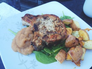 Pan fried thick bone-in pork chops on a bed of spinach, with roasted potatoes, and homemade spiced apple sauce